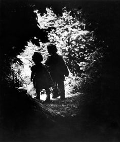 The children of photographer W. Eugene Smith walk hand-in-hand in the woods behind his home, 1946.