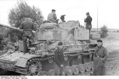 A Panzer 4 with it's crew sitting idle during a break from fighting