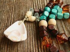 The colors of the earth and sea are combined in this beach inspired, boho summer necklace. A beautiful, eco friendly, wooden beaded necklace with a creamy pink shell pendant and a bronze metal clasp, with it's hand knotted pieces to give it a very beachy boho feel. #acabininparis #beachthemed #bohojewelry #bohemianjewelry #bohemiannecklace #seashelljewelry #seashellnecklace #seashells #woodenjewelry #ecofriendly #woodennecklace #handmadegifts