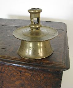 16th Century Brass Capstan Candlestick c.1550-1580, Excellent example of a 16thC. brass capstan candlestick, having typical short sconce with ejection aperture and being peened to the base. The base below the large drip pan with original lathe marks.