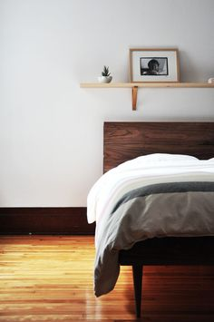 Wooden headboard.  Shelf above bed.