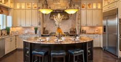 Three stools tucked in the island and two lights frame the range hood and lighted cabinets. From Monterey Homes. The Carillon at The Estates new home community in Southlake, TX. Kitchen Island With Stove, Kitchen Island With Seating, New Kitchen, Kitchen Ideas, Kitchen Designs, Round Kitchen, Kitchen Islands, Kitchen Layout, Kitchen Decor