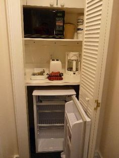 Closet kitchen in the bedroom, with coffee maker, refrigerator, toaster, and microwave in addition to the kitchen in the main living space.