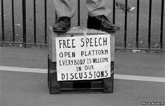 A speaker standing on a milk crate, with a sign advocating free speech, addresses a crowd at Speakers Corner, Hyde Park, London, 1993