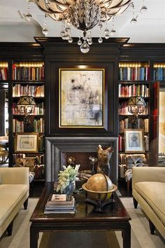 Glamorous living room library with a pair of tan sofas, built-in shelves and crystal chandelier.