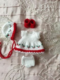 Hand knitted dolls outfit to fit 5 Berenguer Itty Bitty baby doll/Cupcake doll/Christmas outfit. Knitted in white, red and green, and consisting of a dress, bonnet, pants and shoes. The dress is knitted in white and red, and has a Christmas themed row of knitted in holly leaves with