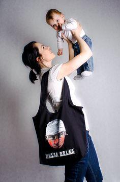 Matka Polka  W czasach politycznego wyścigu, panowania hipermarketów i zagranicznych korporacji Matka Polka to już nie ta sama kobieta. Oryginalna grafika wykonana w 100% sprayem.    Torba zapinana na guzik. Wewnątrz dwie, praktyczne kieszonki na zamek.    100% bawełna, wyprodukowana w Polsce, w zestawie z przypinką, wlepkami i pocztówką.     Zaprojektowany przez: IMP2K