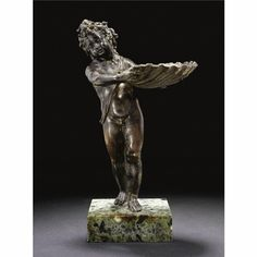 VENETIAN, SECOND HALF 16TH CENTURY  A BRONZE FIGURE OF A PUTTO HOLDING A SHELL