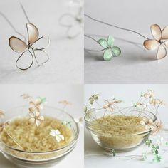 Die bemalten Blumen aufgerecht in einer Glasschüssel voll mit Blumensteckschaum stecken