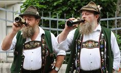 German twin brothers in traditional clothes drink a beer at Oktoberfest 2010
