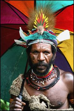 Culture and modernity in Papua New Guinea. A Huli man under a colorful umbrella in the Huli Province of Papua New Guinea. #PapuaNewGuinea