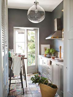 Cocina pequeña con suelo hidráulico y paredes pintadas de color gris oscuro