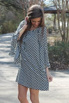 "Chevron alert! Black and white are classic colors that are so easy to accessorize, and we love the chevron look of the pattern on this silky dress. This piece features bell sleeves, a keyhole at the neckline and a simple shift style. Add a statement necklace and heels and you're set!   Fits true to size. Miranda is wearing a small.   From shoulder to hem:  Small - 33.5""  Medium - 34.5""  Large - 35.5"""