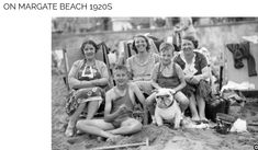 ON MARGATE BEACH 1920S.  On the beach at Margate: three ladies sit in deckchairs, while two boys in bathing costumes sit, one on the sand, one astride a toy bulldog. Pinned by Judi Crowe.