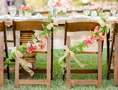 bride and groom seats at the wedding reception with garland on them