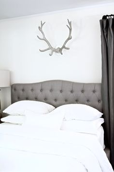 cozy and romantic French farmhouse bedroom reveal via For All Things Lovely | neutral tufted headboard + rustic antlers