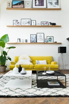 Pretty living room. I like how the artwork is displayed. The sofa really stands out and I love that rug.