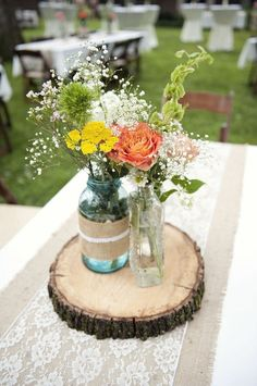 Cute idea for centerpieces with burlap and lace decorated mason jar flower vases on a slice of wood