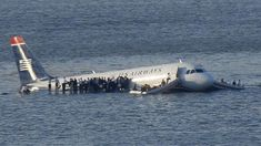 Passengers stand on the wings of a U.S. Airways plane as a ferry pulls up to it after it landed in the Hudson River in New York, January 15, 2009.  Local media said the plane was an Airbus with 146 passengers and five crew which had just taken off from La Guardia Airport and was trying to return after apparently striking a flock of birds.   REUTERS/Brendan McDermid (UNITED STATES)  BEST QUALITY AVAILABLE - RTR23FP8