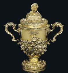 A GEORGE II SILVER-GILT CUP AND COVER MARK OF PAUL DE LAMERIE, LONDON, 1745 Inverted bell shaped and on a spreading foot, the foot and lower body each cast and chased with scrolling foliage, the body further applied with a winged putto holding a bunch of grapes, with two shell capped scroll handles, the detachable cover similarly cast and chased and with a finial cast as a bunch of grapes, later engraved with a coat-of-arms on one side and a crest on the other  sold 87,650 GBP