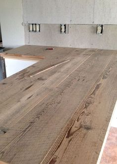 DIY Reclaimed Wood Countertop - gluing and nailing down reclaimed wood boards