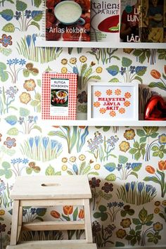 Floral wallpapered wall with shelves and brightly coloured books on it