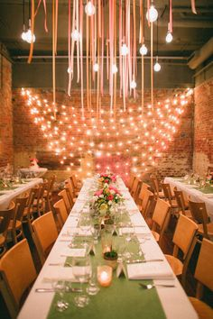 Fun indoor rehearsal dinner with exposed brick, streamers and exposed bulbs