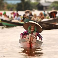 "by Arie Darmana Woman smiling on her ""Jukung"" (boat) at Traditional Floating Market, Lokbaintan, Kalimantan, Indonesia"