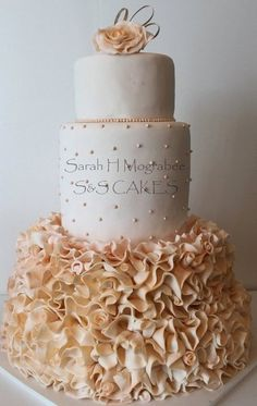 I love how Sarah Mograbee incorporates rosebuds amongst the mass of ruffles on the bottom two tiers of this cake.