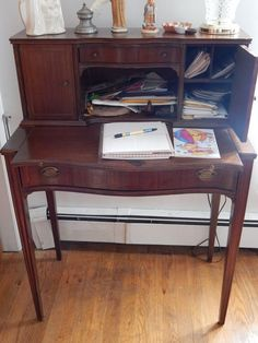 secretary from turn-of-the-early 20th century. It has two side doors, and upper and lower center drawers. The writing surface slides out.