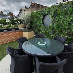 Vibrant funky roof terrace with artificial green wall by The Garden Builders