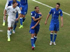 Italy's defender Giorgio Chiellini (C) shows an apparent bitemark by Uruguay forward Luis Suarez during a Group D football match between Italy and Uruguay at the Dunas Arena in Natal during the 2014 FIFA World Cup on June 24, 2014. Uruguay won 1-0.