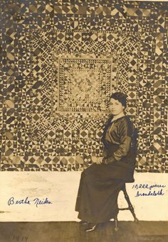 """Bertha Neiden poses proudly with her quilt - writing on the print """"10,222 pieces of broadcloth"""""""