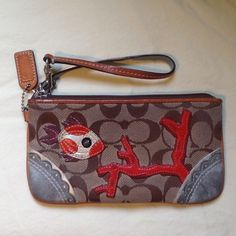 """✨Coach wristlet with fish and coral very cute Very cute brown coach wristlet has some stains/marks inside.  See 3rd picture. Used.Features  *Brown signature jacquard fabric with blue suede trimming * Fish & Coral made with leather , suade  * Silver /nickle hardware * 6 """" strap with dog leash clip * Zip top closure * Coach leather hangtag * blue interior lining  Size 7 1/4 """" L x 4 """" H  Colour  Multi-colour  Original Price $198  No trades or paypal Coach Accessories"""
