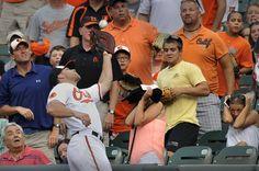 El beisbolista Chris Davis, de los Orioles de Baltimore, llega hasta el público para atrapar una bola en el primer inning de un partido de béisbol contra los Astros de Houston.