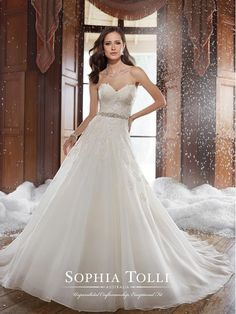Sophia Tolli Y21503: Delicate details create simple elegance in Peyton, a strapless sweetheart fantasy organza gown with lace appliqués and a hand-beaded crystal belt feature. Soft folds in the skirt and chapel length train create a lovely A-line silhouette while a semi sheer back with back corset finishes this sweet gown. Removable spaghetti and halter straps included. Also available with a back zipper.