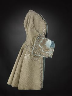 Man's coat of brown figured silk, high neckline with no collar, shaped front and full skirt which is interlined, possibly with horsehair, deep turn-back cuffs faced with pale blue silk, coat lined with pale blue silk, cuffs and pockets trimmed with silver lace: English, about 1740 Museum reference K.2004.88