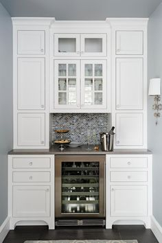 A built-in wine refrigerator turns this butler's pantry into a convenient storage and serving area. The kitchen of this 1920s home got a glam update that preserves its historic feel. Furniture-style feet on the cabinetry are among the period touches that bring character to the space.