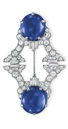 AN ART DECO SAPPHIRE AND DIAMOND JABOT BROOCH - Each terminal set with a circular cabochon sapphire, to the old European and baguette-cut diamond openwork plaque, mounted in platinum, circa 1925.