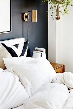 Minimalist bedroom inspiration with a black statement wall, a gold sconce, white bedding, and a black and white throw pillow