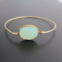 A beautiful large aqua green seafoam chalcedony genuine gemstone has been transformed into a dainty, delicate bangle bracelet with a 14k gold filled band.
