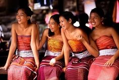 Balinese girls, in their colourful traditional dress, laughing and smiling.. Looking happy..