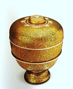 Silver and gold khram lidded water jar on a pedestal tray.