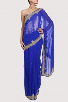 Luxury is redefined with this blue georgette sari teamed with similar blue unstitched blouse. It is richly enriched with golden rhinestones. Get ready to steal the evening draped in this enigmatic creation. (The gold sequined blouse is for styling only)