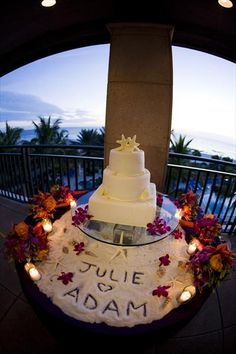 """On the cake table, the cake was raised on a glass platform, and a beach fashioned beneath it, with """"Julie (heart) Adam"""" written in sand in front of the cake. Sand, shells, and purple orchids below the cake were the perfect compliment to the all white confection, complete with two white chocolate starfish on top, representing the happy newlyweds. -- beach theme?"""
