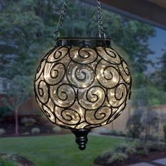 An elegant Clear Solar Glass Ball surrounded by a beautiful metal scroll design sets this gorgeous hanging lantern apart! A glow will automatically illuminate from within the ball at dusk with its string of 15 Solar powered firefly lights. Adds a dazzling touch to your garden! Outside Hanging Lights, Hanging Lantern Lights, Lanterns Decor, String Lights, Solar Powered Led Lights, Solar Lights, Outdoor Solar Lanterns, Hanging Bird Cage, Vegetable Gardening