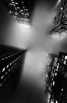 Ernst Haas.  At such an extreme shot, fog overwhelms the buildings creating darkness and heling the bright lights of the buildings to stand out. Recreation and influence of this image can be the angle of laying on my back and shooting the camera straight above. The rule of thirds is applied.