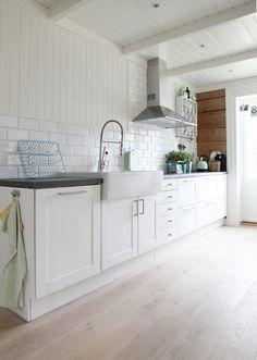 UNDERBARE: Kjøkken uten overskap er moderne. Det gir et ryddig og effektivt inntrykk, og så lenge man har god plass til underskap får man likevel plass til det man trenger. Denne modellen er fra Ikea, supplert med enkle metrofliser og gammel panel.