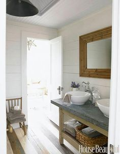 """Rustic Bathroom """"This bathroom console in the guesthouse was an antiques fair find,"""" says designer Ginger Barber. """"It's all about the back and forth, crisp white vessel sinks and white walls against the worn zinc top and rustic baskets."""""""