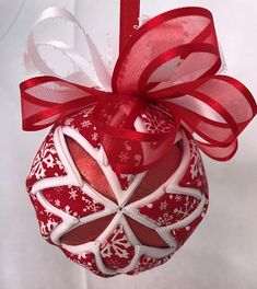 Red and white snowflake cotton fabric, white solid cotton and red lame fabric. Decorative ribbon added with a ribbon hanger. Folded cotton fabric squares pinned on a 3 polystyrene ball. No sew. All of my items come from a smoke/pet free home. Metal hanger not included. I